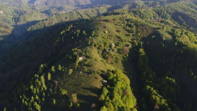 vidéos et rushes de vue aérienne au-dessus du village de montagne avec des arbres verts en fleurs au lever du soleil avec la lumière du soleil lumineuse. - romania