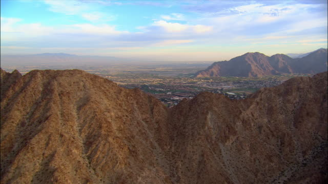 aerial view over mountains to reveal city in background / palm springs, california - palm springs california stock videos & royalty-free footage