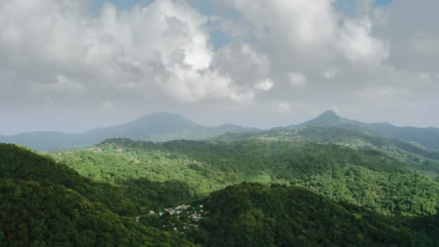 vidéos et rushes de aerial view over mountains with dense green forest, hilltop settlements and clouds on the horizon (saint lucia) - arbre tropical