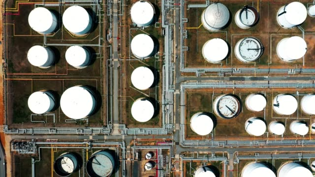 aerial view over oil refinery or chemical factory with many storage tanks - oil industry stock videos & royalty-free footage