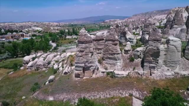 vídeos de stock e filmes b-roll de aerial view over open landscape with rocks, flora - exposto ao ar