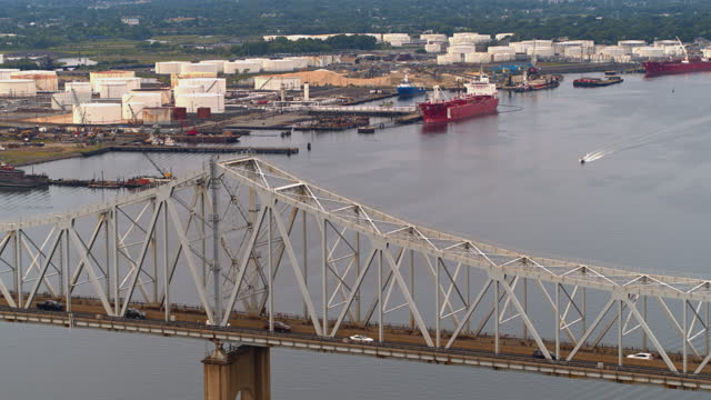 aerial view over outerbridge crossing bridge on the industrial cargo ship unloading at the petroleum terminal in new jersey, on the arthur kill tidal strait at the border with new york state. drone video with the forward camera motion. - anchored stock videos & royalty-free footage