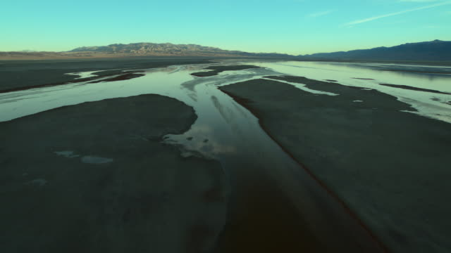 aerial view over owens lake, a mostly dry lake bed since the owens river was diverted to provide water to the los angeles area in 1913. - salt flat stock videos & royalty-free footage