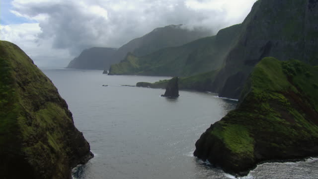 Aerial view over Pacific of Molokai's mountainous coastline and small islets near Haupu Bay.