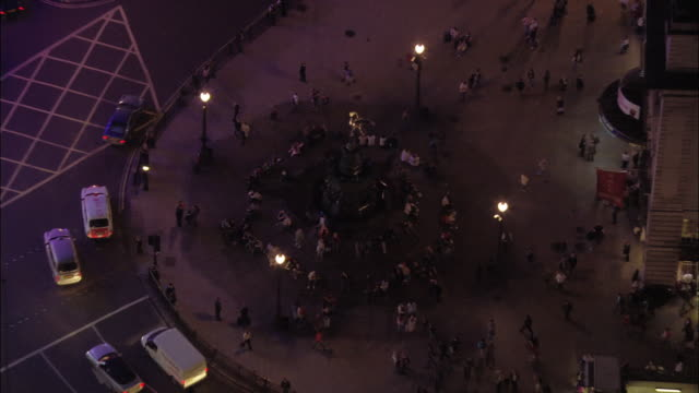 vidéos et rushes de aerial view over people sitting around the eros statue / zoom out to traffic around piccadilly circus at night / london, england - place
