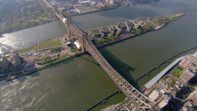 aerial view over queensboro bridge from manhattan over roosevelt island to long island city in queens / new york city, new york - cantilever bridge stock videos & royalty-free footage