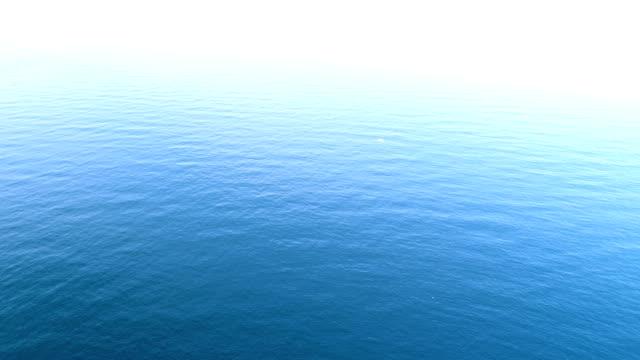 Aerial view over quiet turquoise ocean water.