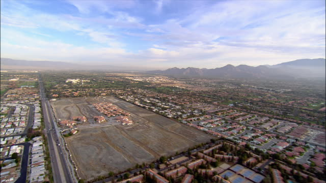 aerial view over residential neighborhoods with mountains in background / over golf course and tennis courts / palm springs, california - palm springs california stock videos & royalty-free footage