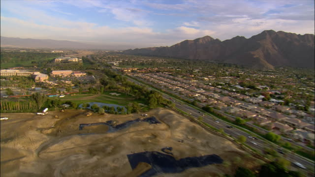 aerial view over residential neighborhoods with mountains in background / over golf courses and tennis courts / palm springs, california - palm springs california pool stock videos & royalty-free footage