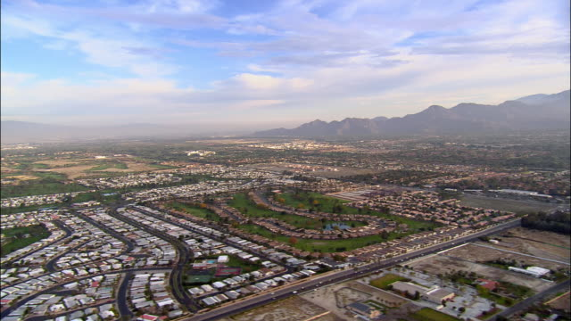 Aerial view over residential neighborhoods with mountains in background / Palm Springs, California
