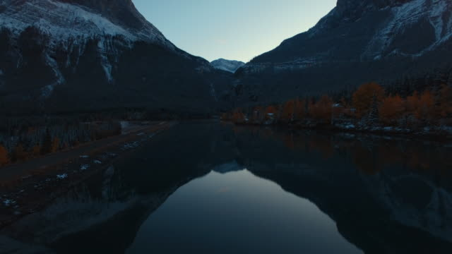 aerial (drone) view over river and snow-covered mountains at dusk - snowcapped mountain stock videos & royalty-free footage