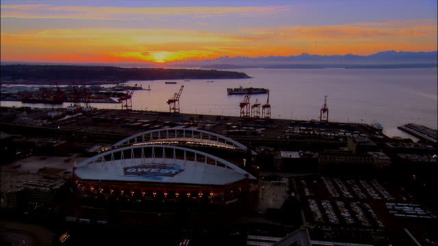 aerial view over safeco field and qwest field and downtown as sun sets over puget sound / seattle, washington - コロンビアセンター点の映像素材/bロール