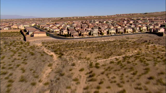 Aerial view over sagebrush towards housing development / over rows of tract housing / Las Vegas, Nevada