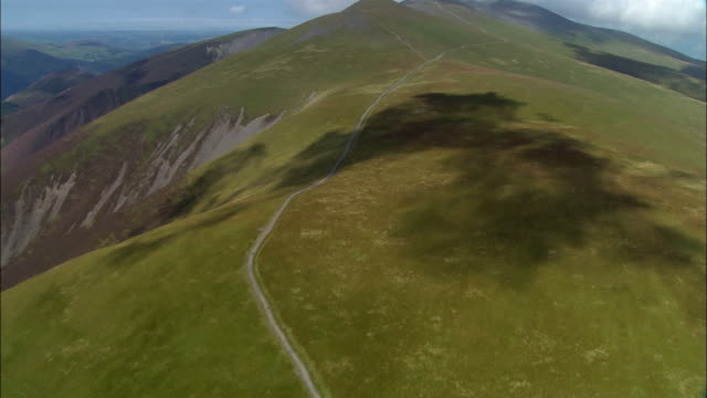 Aerial view over Skiddaw Mountain in the Lake District / clouds casting shadow as they pass overhead / Cumbria, England