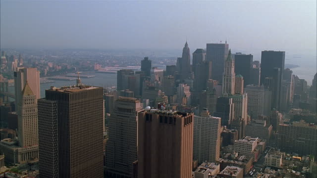 aerial view over skyscrapers in lower manhattan towards hudson river / statue of liberty in new york harbor / new york city - 2002 stock videos & royalty-free footage