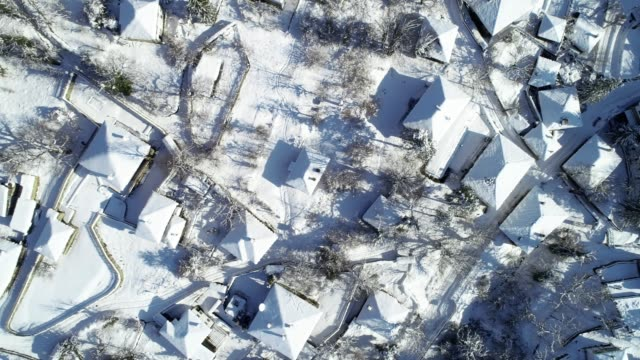 aerial view over small authentic european mountain village surrounded by woodlands, deep snow cover, different points of view, snowcapped roofs, old authentic houses - deep snow stock videos & royalty-free footage