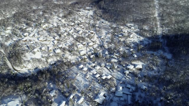 aerial view over small authentic european mountain village surrounded by woodlands, deep snow cover, different points of view, snowcapped roofs, old authentic houses - ski flying stock videos and b-roll footage