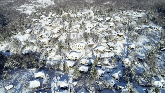 aerial view over small authentic european mountain village surrounded by woodlands, deep snow cover, different points of view, snowcapped roofs, old authentic houses - idyllic stock videos & royalty-free footage