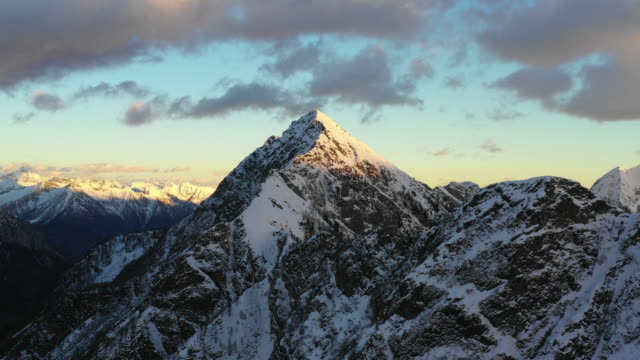 aerial view over snow covered high mountains at sunset - snowcapped mountain stock videos & royalty-free footage