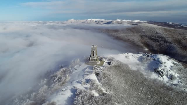 aerial view over snowcapped mountain peak, architectural monument on top, wintertime, cultural and historical heritage, shipka monument, independence day - monument stock videos & royalty-free footage