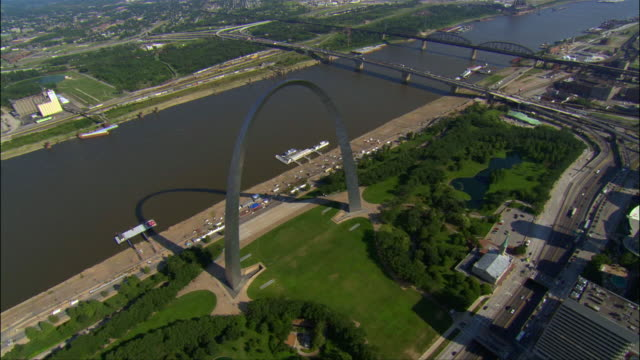Aerial view over the Gateway Arch / zoom out to reveal Mississippi River and downtown area / St. Louis, River