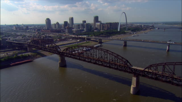 stockvideo's en b-roll-footage met aerial view over the macarthur and poplar street bridges crossing the mississippi river / downtown area and the gateway arch in background / st. louis, missouri - st. louis