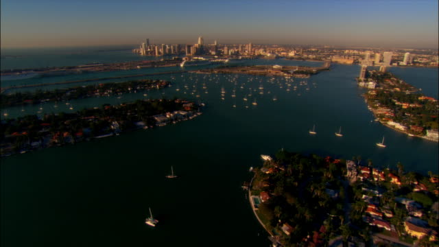 aerial view over the venetian islands and the venetian causeway in biscayne bay / over skyscrapers downtown / miami, florida - venetian causeway bridge stock videos & royalty-free footage