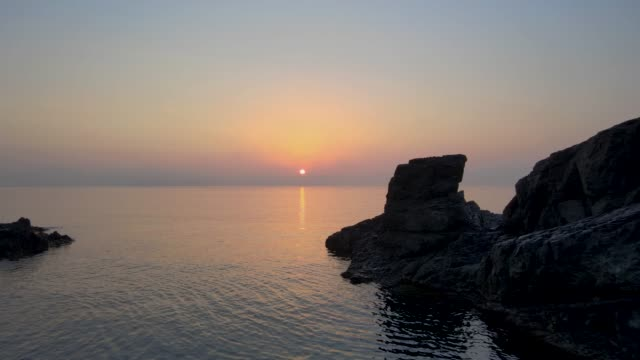 aerial view over the water towards the sun with rocks backlighted. - agua点の映像素材/bロール