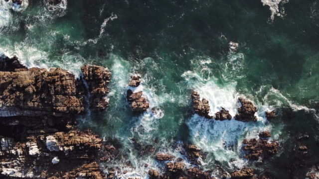 aerial view over the waves crashing against the rocks - rock face stock videos and b-roll footage