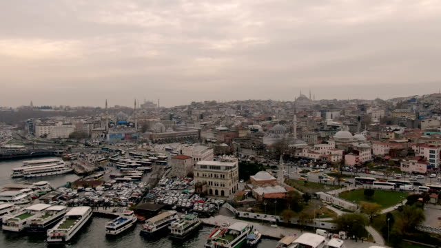aerial view over   the yeni camii, eminonu square and rüstem pasha mosque, ottoman mosque from the 16th century decorated with a wide range of floral & geometric tile designs -  istanbul, turkey - bazar delle spezie video stock e b–roll