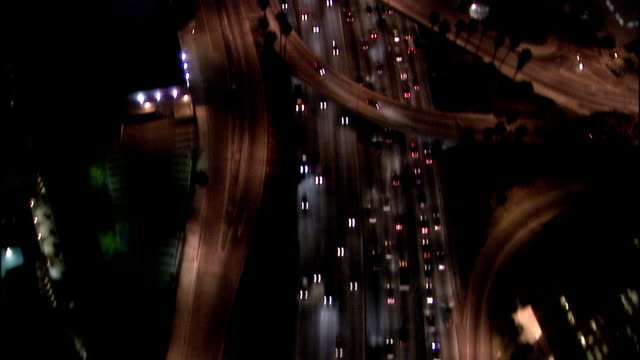 Aerial view over traffic driving on downtown highway at night / Los Angeles, California
