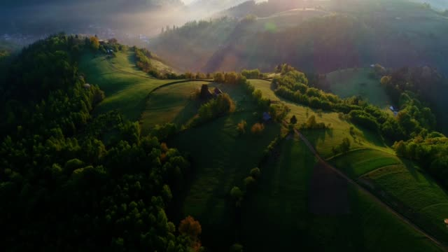 vídeos de stock e filmes b-roll de aerial view over transylvania green fields, mountain village at sunrise, bright sunlight, small houses, springtime, greenery, carpathian mountains, majestic view, travel destinations - roménia