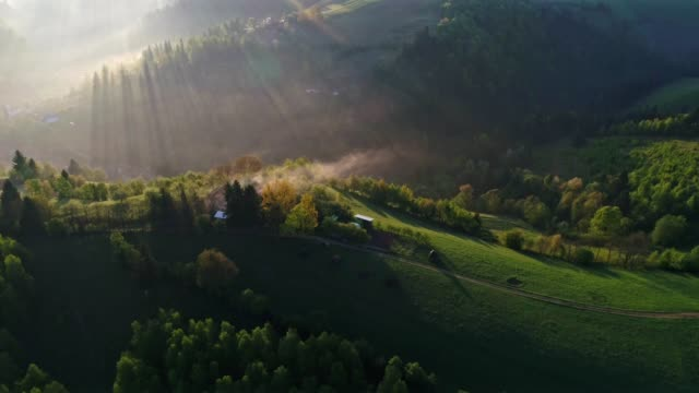 vídeos de stock e filmes b-roll de aerial view over transylvania green fields, mountain village at sunrise, bright sunlight, small houses, springtime, greenery, carpathian mountains, majestic view, travel destinations - horizontal