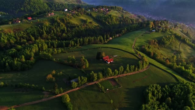 aerial view over transylvania green fields, mountain village at sunrise, bright sunlight, small houses, springtime, greenery, carpathian mountains, majestic view, travel destinations - romania stock videos & royalty-free footage