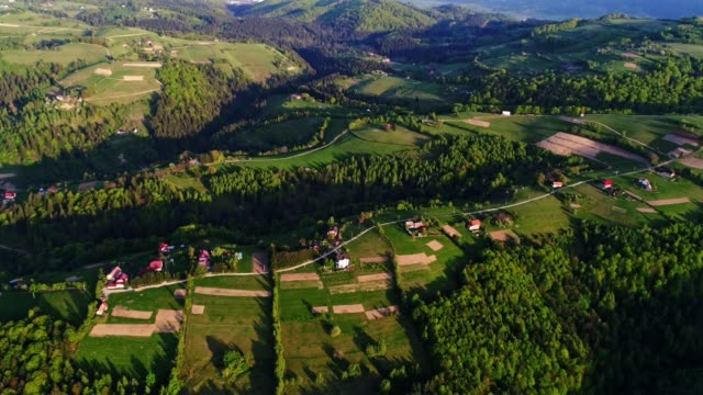 Aerial view over Transylvania green fields, mountain village at sunrise, bright sunlight, small houses, springtime, greenery, Carpathian mountains, majestic view, travel destinations