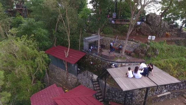 Aerial view pan left to right visitors pose for photographs on a platform at the Kalibiru Tourism Village in this aerial video taken at Kulon Progo...