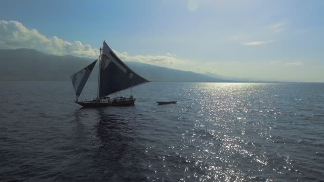 Aerial View Panning Around a Sailboat on the Open Ocean with Mountains Behind
