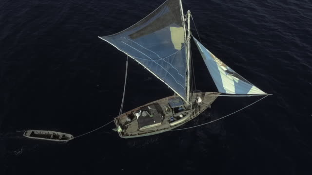 aerial view panning around a small sailing boat on a dark ocean - white dress stock videos & royalty-free footage