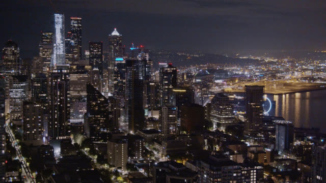 aerial view panning shot of the seattle skyline and puget sound (elliott bay) at night - water's edge stock videos & royalty-free footage