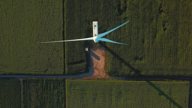 Aerial view passing directly above a wind turbine in agricultural field