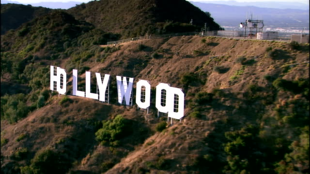 aerial view past hollywood sign / los angeles, california - kalifornien stock-videos und b-roll-filmmaterial