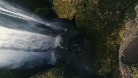 ms aerial view people standing below rugged waterfall,iceland - zoom out stock videos & royalty-free footage