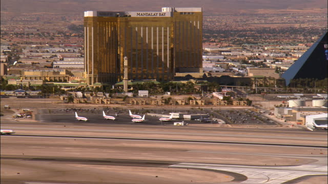 aerial view planes parked at mccarran airport with mandalay bay hotel in background / plane taxiing on runway / las vegas, nevada - mandalay bay resort and casino stock videos & royalty-free footage