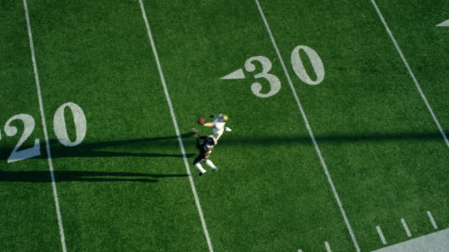 WS Aerial view Professional football defensive back tipping pass away from running back attempting to catch pass