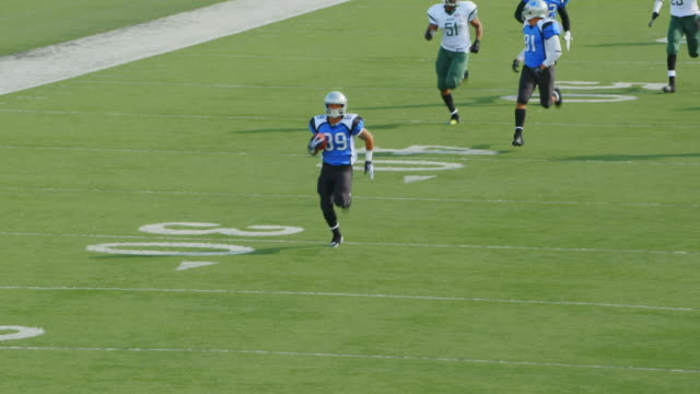ws aerial view. professional football player runs with football, prances into end zone for touchdown, and jumps into the air with teammates. - amerikanischer football stock-videos und b-roll-filmmaterial