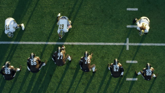 MS Aerial view Professional football quarterback calling play in huddle and taking snap in shotgun position