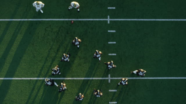 WS PAN Aerial view Professional football quarterback calling play in huddle and taking snap and throwing pass from shotgun position