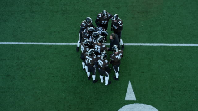 ms ts aerial view professional football team getting play from coach during timeout - アメリカンフットボールヘルメット点の映像素材/bロール