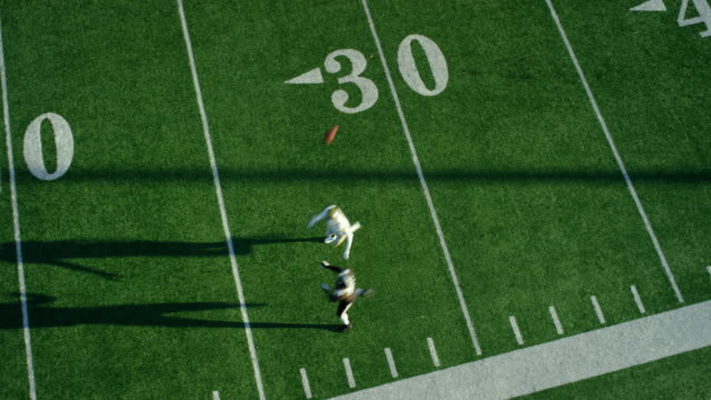 WS Aerial view Professional football wide receiver running down sideline covered by defensive back and catching pass
