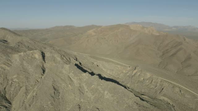 aerial view remote desert mountain range mojave desert - 荒野点の映像素材/bロール